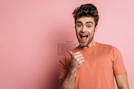 Photo for Excited man pointing with thumb while looking at camera on pink background - Royalty Free Image