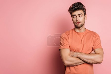 Photo for Offended young man standing with crossed arms and looking away on pink background - Royalty Free Image