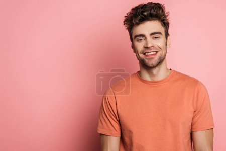 happy, handsome young man smiling at camera on pink background