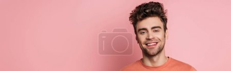 Photo for Panoramic shot of happy young man smiling at camera on pink background - Royalty Free Image