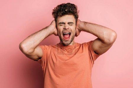 Photo pour Jeune homme irrité criant et couvrant les oreilles avec les mains sur fond rose - image libre de droit