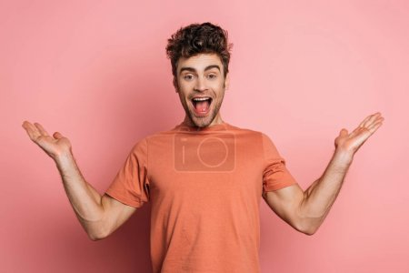 Photo for Excited young man laughing at camera while standing with open arms on pink background - Royalty Free Image
