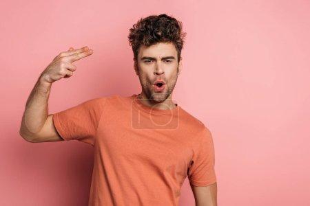 Photo pour Un jeune homme imitant l'autodestruction en tirant sur un fond rose - image libre de droit