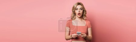 panoramic shot of shocked girl looking at camera while chatting on smartphone on pink background