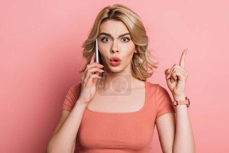 Photo pour Une fille choquée fait un geste d'idée en parlant sur un smartphone en arrière-plan rose - image libre de droit