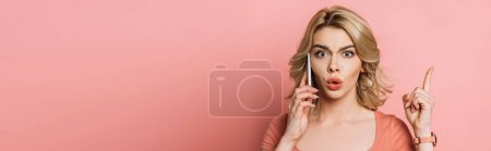 Photo for Panoramic shot of shocked girl showing idea gesture while talking on smartphone on pink background - Royalty Free Image