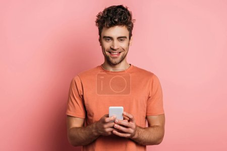Photo for Positive young man smiling at camera while chatting on smartphone on pink background - Royalty Free Image