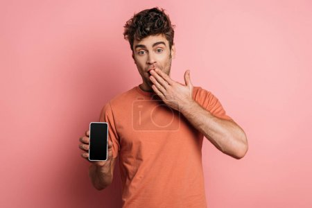 Photo for Shocked young man covering mouth with hand while showing smartphone with blank screen on pink background - Royalty Free Image