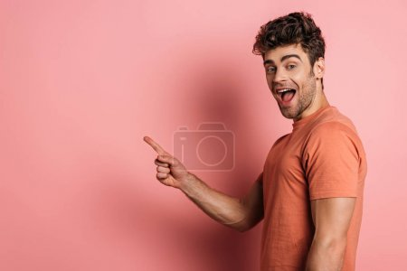 Photo for Excited young man pointing with finger while looking at camera on pink background - Royalty Free Image