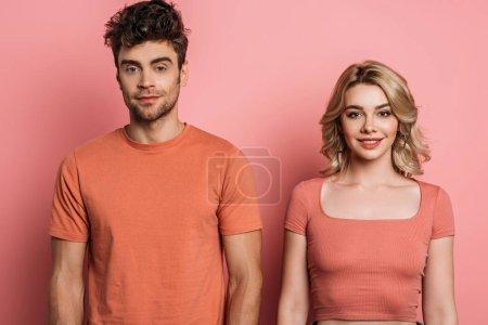 Foto de Joven, hombre y mujer positiva mirando a la cámara en el fondo rosa - Imagen libre de derechos