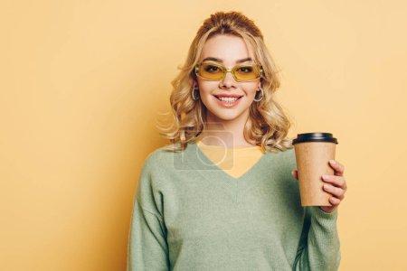 Photo pour Attrayant, fille à la mode tenant café pour aller et souriant à la caméra sur fond jaune - image libre de droit