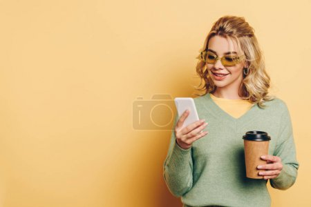 Photo for Smiling girl chatting on smartphone and holding coffee to go on yellow background - Royalty Free Image