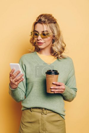Photo for Stylish, smiling girl holding coffee to go while chatting on smartphone on yellow background - Royalty Free Image