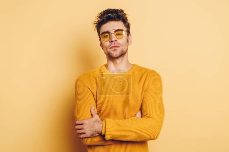 Photo for Handsome, confident man looking at camera while standing with crossed arms on yellow background - Royalty Free Image