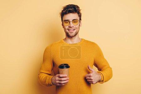 Photo pour Beau jeune homme souriant à la caméra tout en montrant pouce vers le haut et tenant du café pour aller sur fond jaune - image libre de droit
