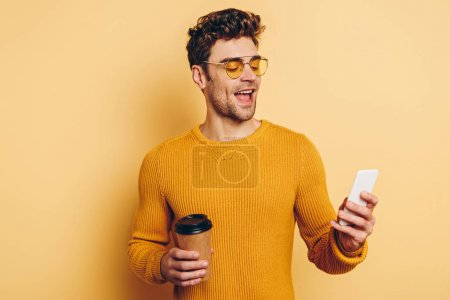 Photo for Cheerful man chatting on smartphone while holding coffee to go on yellow background - Royalty Free Image