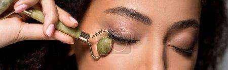 Photo pour Plan panoramique de fille afro-américaine avec les yeux fermés à l'aide d'un rouleau de jade, sur gris - image libre de droit