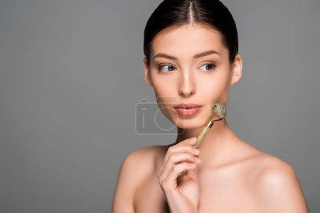 Photo pour Belle fille nue en utilisant le rouleau de massage jade, isolé sur gris - image libre de droit