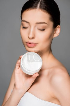 Photo pour Belle fille aux yeux fermés tenant crème hydratante, isolée sur gris - image libre de droit