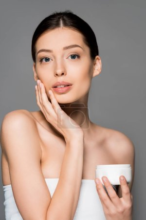 Photo pour Belle fille tendre appliquant crème visage, isolé sur gris - image libre de droit