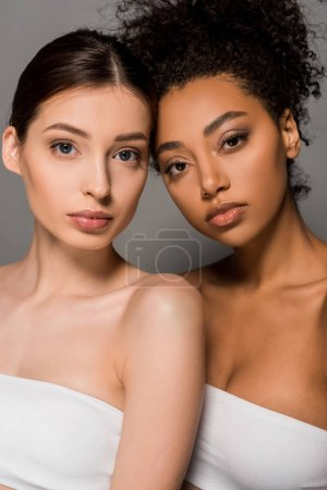 portrait of multicultural girls looking at camera, isolated on grey