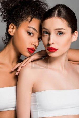 Photo pour Belles femmes multiculturelles aux lèvres rouges, isolées sur grises - image libre de droit