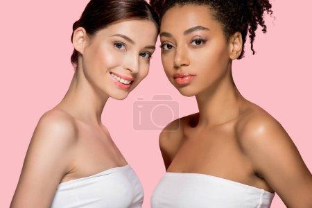Photo pour Portrait de filles multiculturelles souriantes à la peau propre, isolées sur rose - image libre de droit