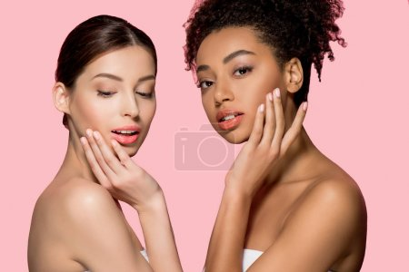 portrait of tender multicultural girls with clean skin, isolated on pink