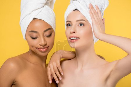 Photo for Multiethnic young woman with towels on heads, isolated on yellow - Royalty Free Image
