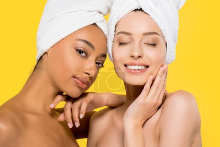 smiling multiracial young woman with towels on heads, isolated on yellow