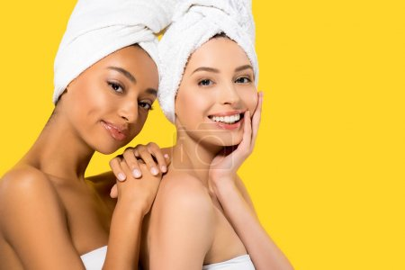 Photo for Portrait of smiling multiethnic girls with towels on heads, isolated on yellow - Royalty Free Image