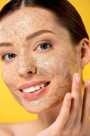Photo pour Portrait de jeune femme heureuse appliquant masque peeling, isolé sur jaune - image libre de droit