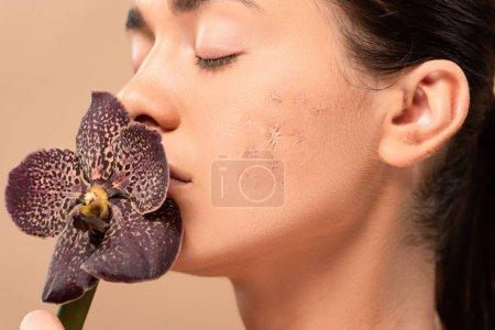 Photo pour Jeune femme avec problème peau odeur orchidée isolé sur beige - image libre de droit