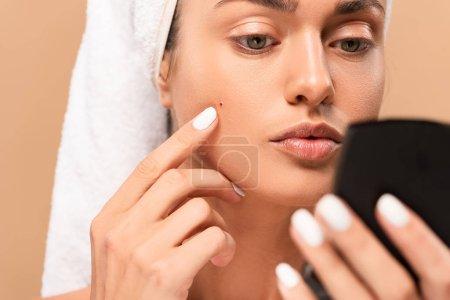 Photo pour Focus sélectif de la femme touchant le visage avec le bouton et regardant le miroir isolé sur beige - image libre de droit