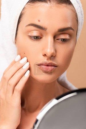 Photo pour Foyer sélectif de la fille dans la serviette toucher le visage avec des boutons et en regardant miroir isolé sur beige - image libre de droit