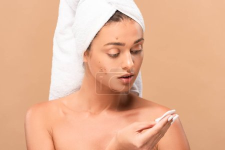 Photo for Young naked woman in towel looking at cotton pad isolated on beige - Royalty Free Image