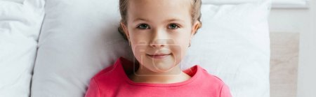 Photo for Panoramic shot of adorable kid sitting on bed and looking at camera - Royalty Free Image