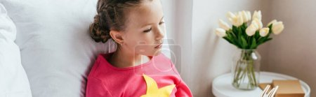 Photo for Panoramic shot of adorable kid reading book while sitting on bed - Royalty Free Image