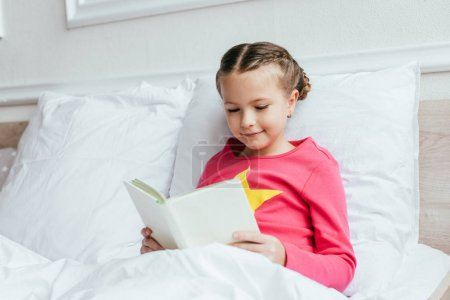 adorable smiling child reading book while sitting on bed