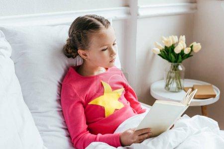 Photo pour Enfant livre de lecture tout en étant assis sur le lit - image libre de droit