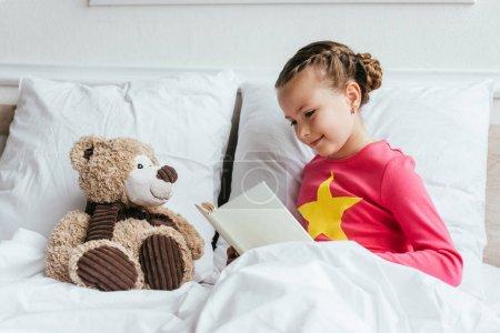 Photo pour Adorable livre de lecture pour enfant à ours en peluche assis sur le lit - image libre de droit