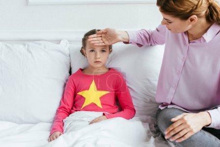 Photo pour Mère touchant le front de malade bouleversé fille avec de la fièvre - image libre de droit