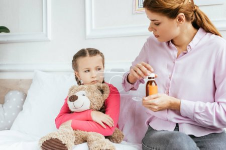 Photo pour Mère donnant sirop à fille malade triste avec ours en peluche - image libre de droit