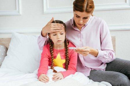Photo pour Mère regardant thermomètre tout en touchant le front de fille malade avec de la fièvre - image libre de droit