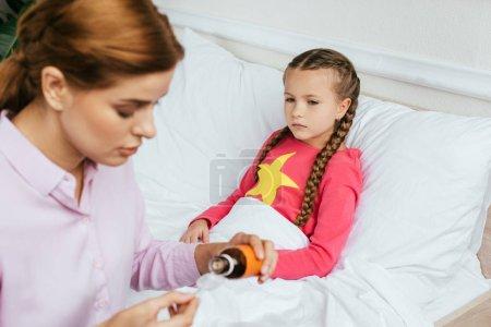 Photo pour Mère inquiète donnant du sirop à sa fille malade au lit - image libre de droit