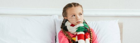 Photo pour Plan panoramique d'enfant malade bouleversé dans l'écharpe assis sur le lit - image libre de droit