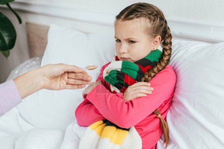 Photo for Mother giving syrup to offended ill daughter with scarf in bed - Royalty Free Image