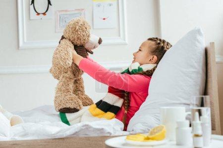 Photo pour Heureux enfant malade dans l'écharpe tenant ours en peluche sur le lit avec des médicaments près - image libre de droit