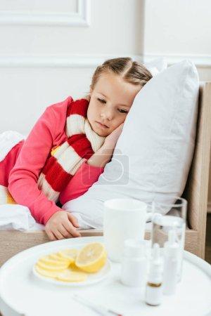 Photo pour Triste enfant malade dans l'écharpe couché sur le lit avec des médicaments près - image libre de droit