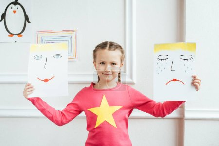 Photo for Cheerful child holding two paintings with happy and sad faces - Royalty Free Image